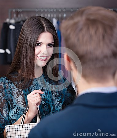 Smiling young girl speaks to shop assistant