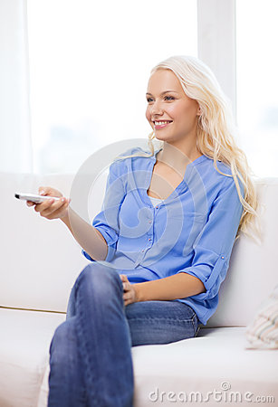 Smiling young girl with tv remote control at home