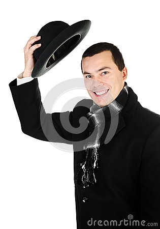 Smiling young man in black coat and scarf holding the hat isolat