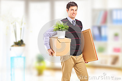 A smiling young man with boxes moving in an apartment
