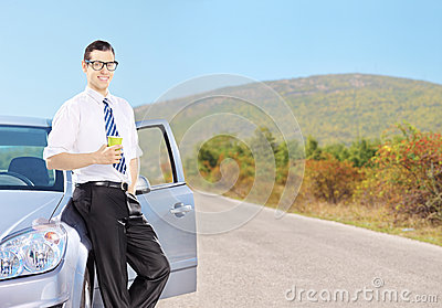 Smiling young man on his automobile relaxing and drinking coffee