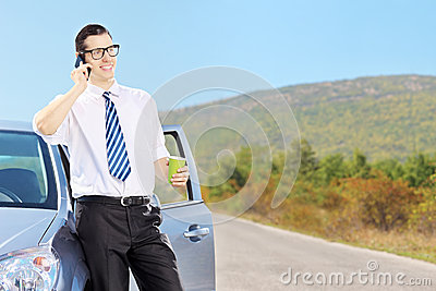 Smiling young man on his automobile talking on a phone and drink