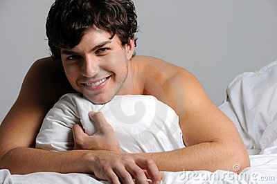 smiling young man lying in bed