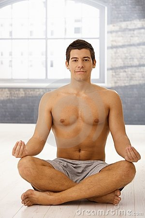 Smiling young man meditating