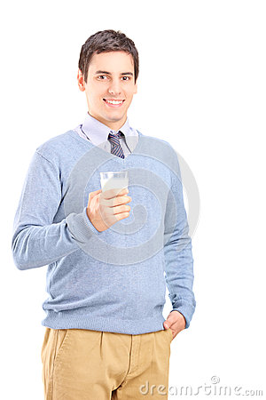Smiling young man posing with a glass of milk