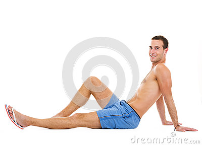 Smiling young man sitting and tanning
