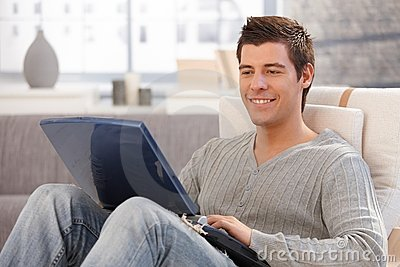 Smiling young man using computer in armchair
