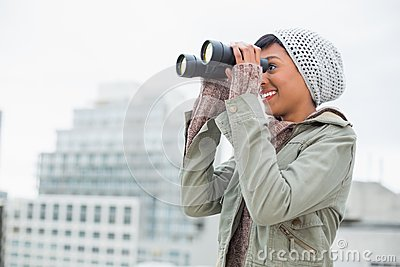 Smiling young model in winter clothes watching with binoculars