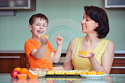 Smiling young mother and son baking muffins