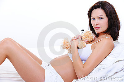 Smiling young pregnant female with teddy toy