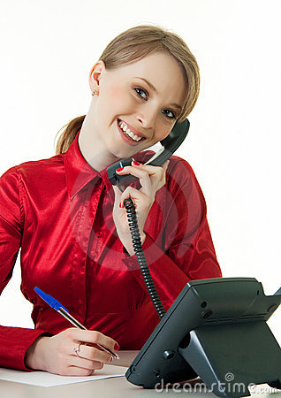 Smiling young receptionist using desk phone