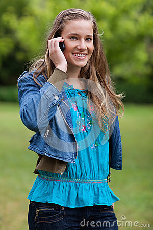 Smiling young relaxed girl talking on the phone