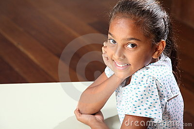 Smiling young school girl 10 sitting in classroom