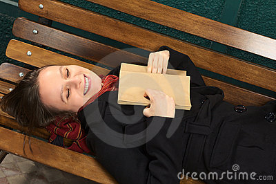 Smiling Young Woman on a Bench with Book