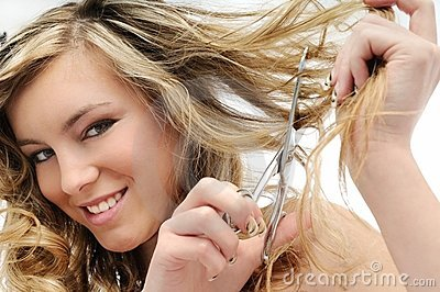 Smiling young woman cutting hair