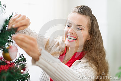 Smiling young woman decorating Christmas tree