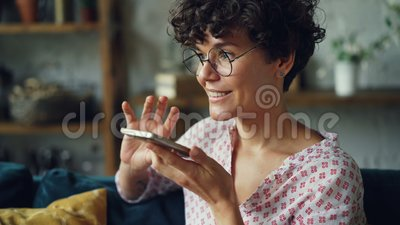 Smiling young woman is dialing telephone number then talking in loudspeaker mode holding smartphone in hand. Modern. Technology, people and communication stock video footage
