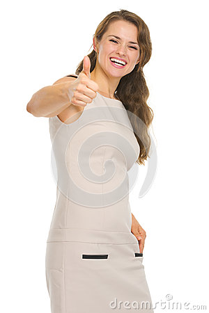 Smiling young woman in dress showing thumbs up