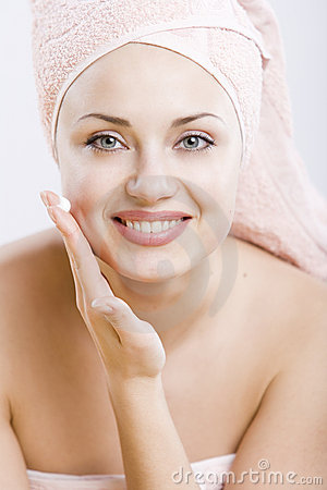 Smiling young woman with facial cream on her hand