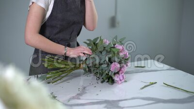 Smiling young woman florist wearing apron talking on mobile phone with customer. Smiling young woman florist wearing apron talking on mobile phone with customer stock footage