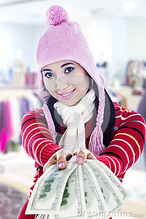 Smiling young woman giving dollar bills
