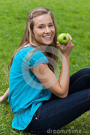 Smiling young woman holding a green apple