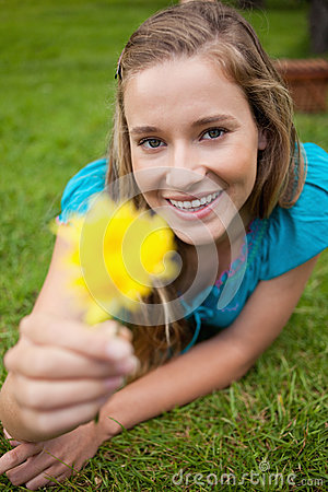 Smiling young woman holding a yellow flower