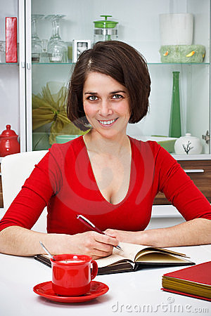 Smiling young woman at home writing