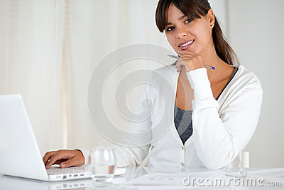 Smiling young woman looking at you using laptop
