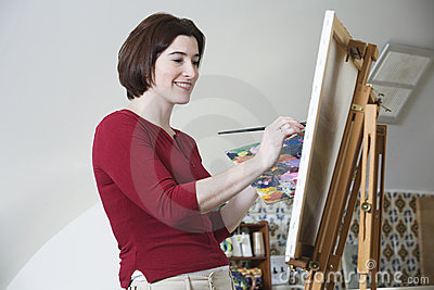 Smiling young woman painting.