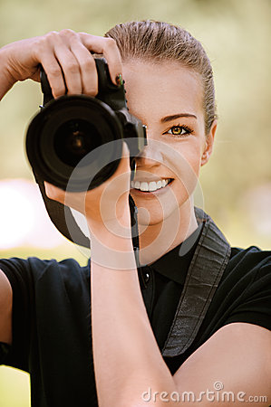 Smiling young woman photographs on
