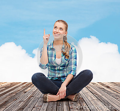 Smiling young woman pointing finger up Stock Photo