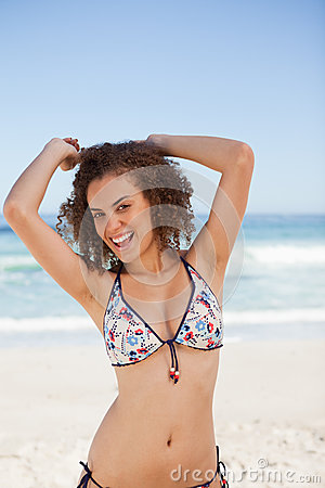 Smiling young woman raising her arms above the head in front of
