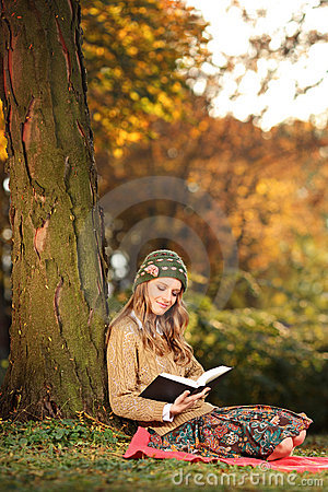 Smiling young woman reading a book