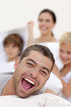 Smilling family having a pillow fight