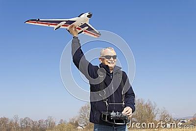 Smilling happy senior RC modeller launching plane