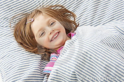 Smilling little girl in the bed