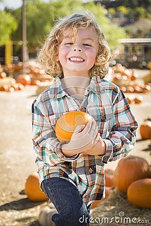 Smilng Boy Holding His Pumpkin at a Pumpkin Patch