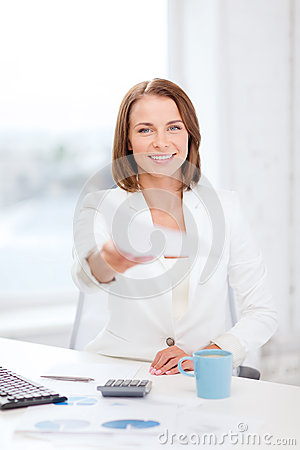 Sming businesswoman giving papers in office