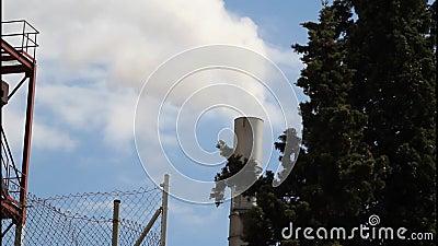 Smokestack of industrial building behind tree stock footage