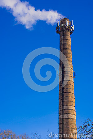 Smoking brick tower with mobile antenna on top