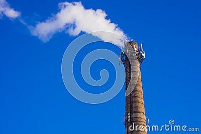 Smoking brick tower with mobile antenna on top