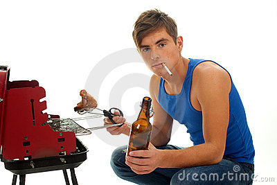 Smoking young man with beer grilling chiken