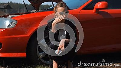 Smutna dziewczyna blisko czerwień łamającego samochodu zbiory