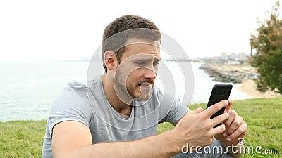 Smutny chłopak narzeka na sprawdzanie zawartości telefonu zdjęcie wideo