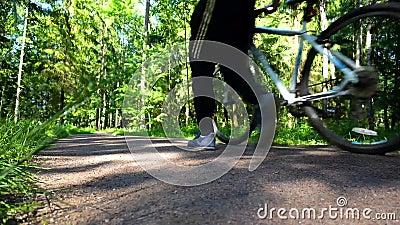 Snijdend van 5 scènes, waar een fietser langs een bosweg berijdt stock footage
