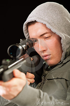 Sniper in hood aims at rifle