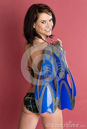Snorkeler female holding flippers wearing bikini