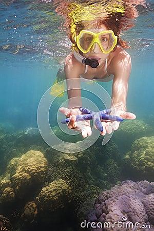 Snorkeler showing blue starfish