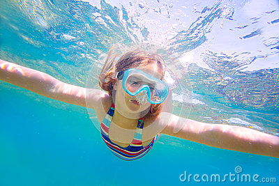 Snorkeling blond kid girl underwater goggles and swimsuit